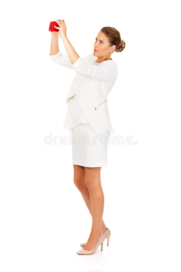 Shocked businesswoman looking into her empty wallet stock photo