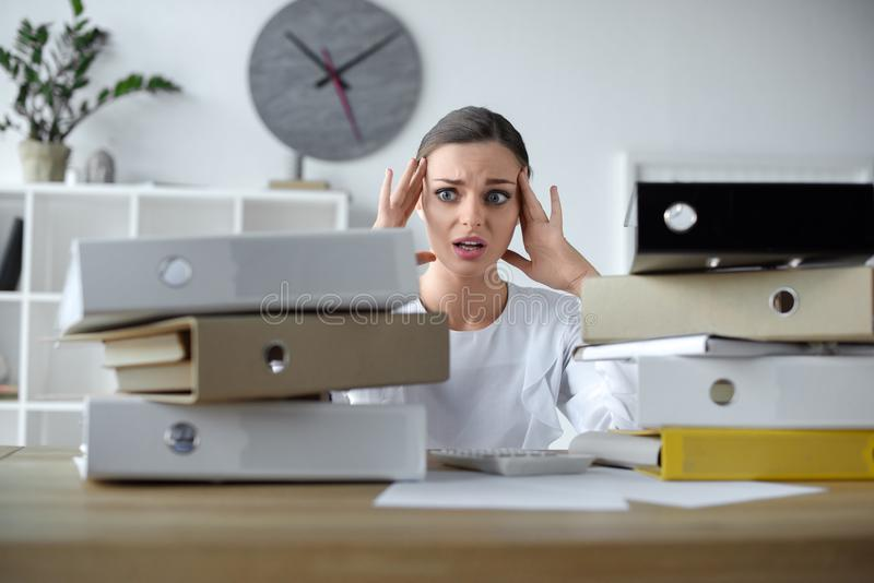 Shocked businesswoman sitting at office desk with stacks of folders. On it royalty free stock image