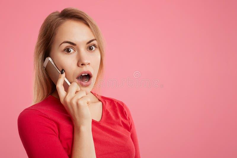 Shocked confundiu a fêmea nova tem a conversa telefônica através do telefone, surpreendido ouvir notícia inesperada, isolada sobr imagens de stock royalty free