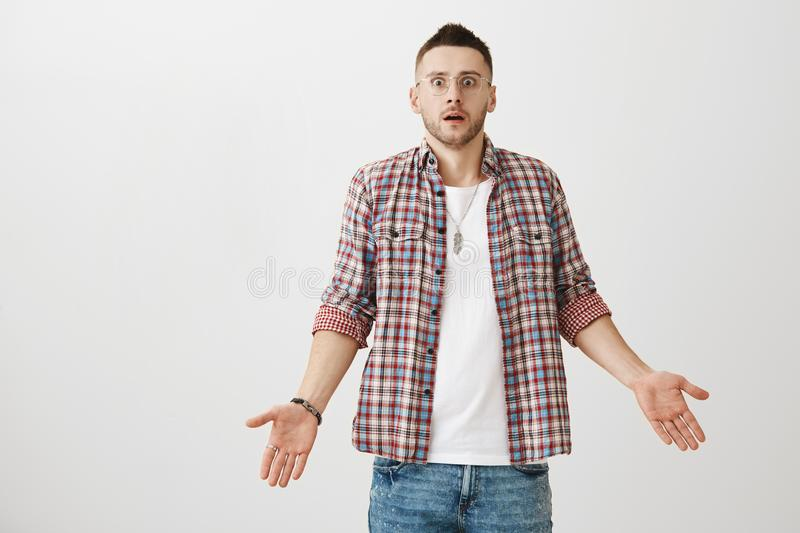 Shocked and confused caucasian male model in glasses and trendy outfit standing with spread palms and opened mouth. Being stunned and caught off guard. Guy did royalty free stock photography
