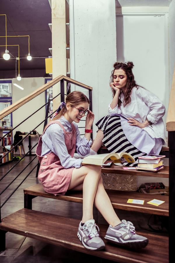 Busy good-looking girls spending time on wooden stairs in co-working area royalty free stock images