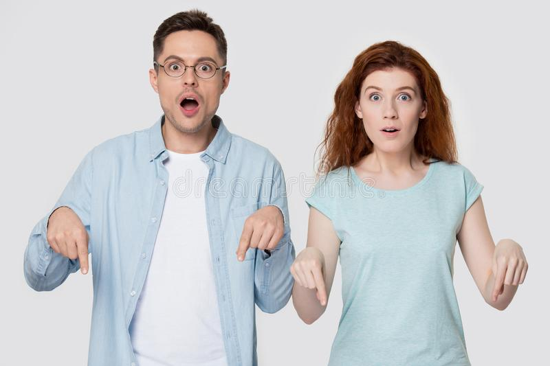 Shocked couple isolated on studio background point down. Surprised young man and woman in casual clothes isolated on grey studio background point downward with stock photo