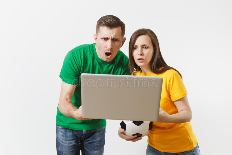 Shocked couple woman man, football fans in yellow green t-shirt cheer up support team with soccer ball, watching game on royalty free stock photo