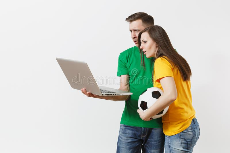 Shocked couple woman man, football fans in yellow green t-shirt cheer up support team with soccer ball, watching game on stock photo