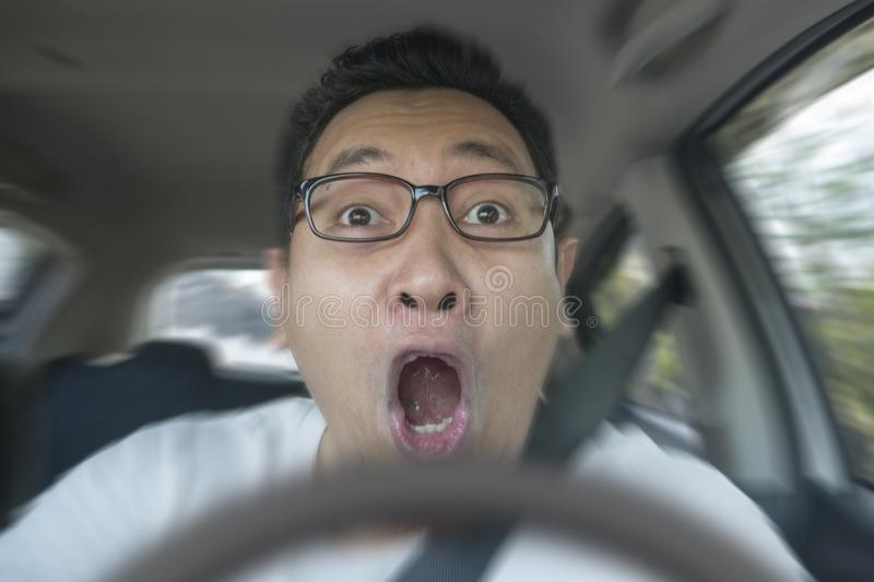Shocked Driver About To Have Accident. Portrait of male Asian driver shocked and panic about to have crash accident, close up with open mouth indonesian royalty free stock image