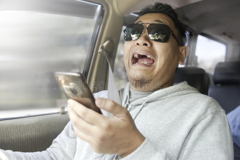 Shocked Driver About To Have Accident. Portrait of male Asian driver shocked and panic about to have crash accident, distracted by phone while driving concept royalty free stock images