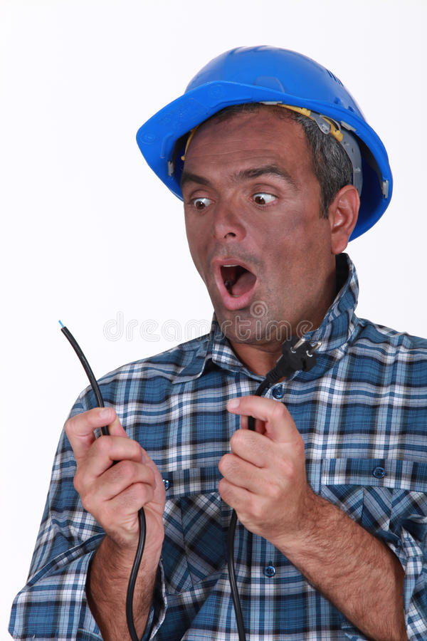 Shocked electrician. Holding live wire stock image