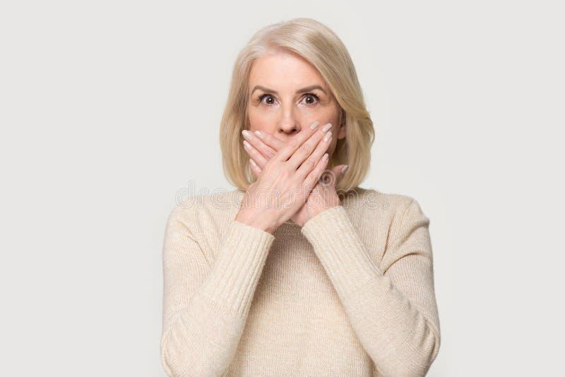 Shocked envelheceu a boca de coberta fêmea com mãos sente assustado fotos de stock