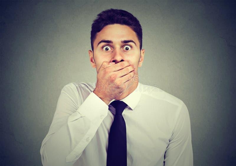 Shocked erschrak den jungen Mann, der seinen Mund mit seiner Hand bedeckt stockfotos