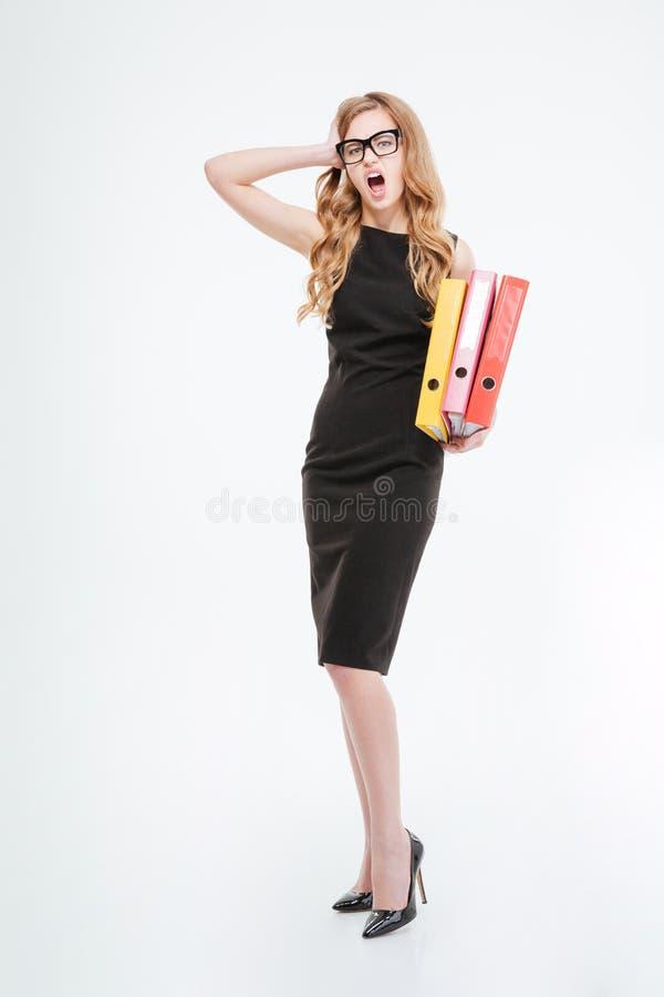 Shocked erstaunte die junge Geschäftsfrau, die Ordner steht und hält lizenzfreies stockbild