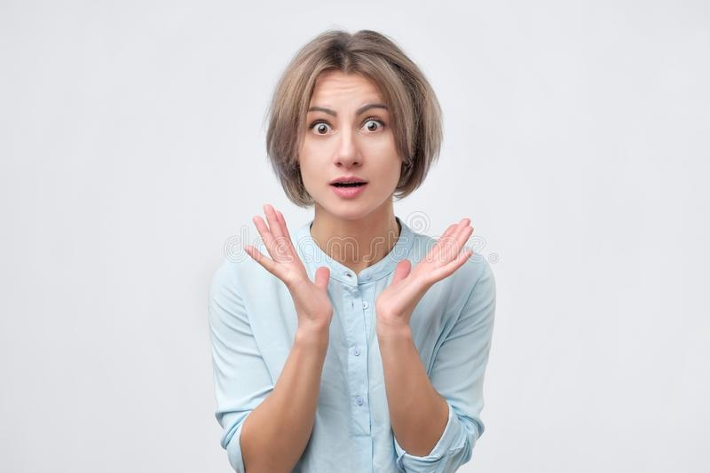 Shocked excited young lady standing isolated over white background. stock image