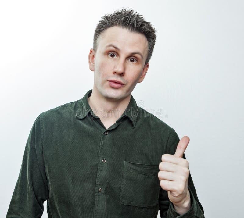 Shocked fassungsloser junger Mann, der beiseite Finger auf die unglaubliche Darstellung der leeren Kopienraum-Werbung zeigt, erst lizenzfreies stockbild