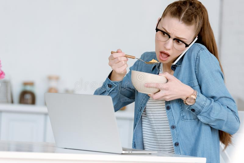Shocked female teleworker eating breakfast while talking on smartphone and looking. On laptop stock photography