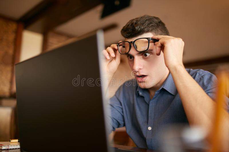 Shocked freelancer hipster man looks to laptop screen and can not believe unpleasant news. Pop-eyed frightened stock image