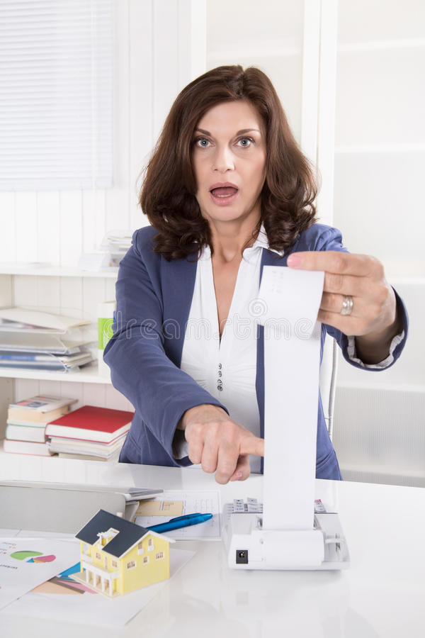 Shocked and frustrated business woman controlling expenses. stock image