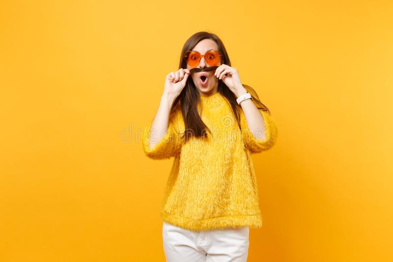 Shocked funny young woman in sweater, white pants, heart orange glasses holding hair like mustache isolated on bright. Yellow background. People sincere stock photo