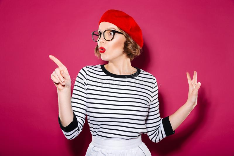 Shocked ginger woman in eyeglasses pointing and looking away royalty free stock photos
