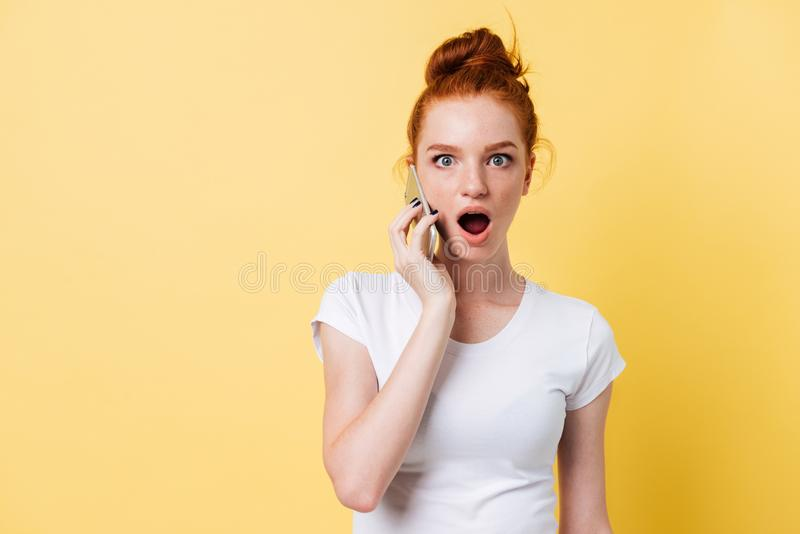 Shocked ginger woman in white t-shirt talking by the smartphone. And looking at the camera over yellow background royalty free stock photos
