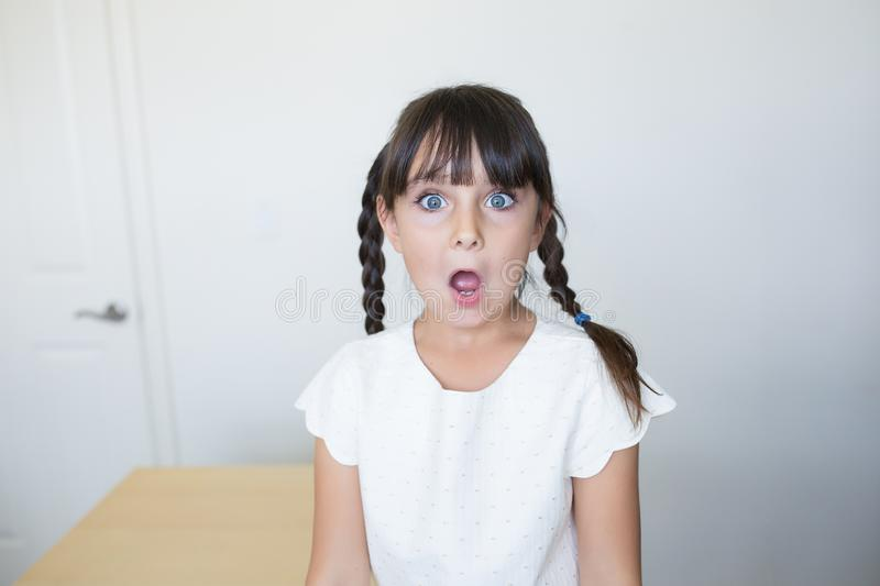 Shocked girl is looking at the camera with big eyes and open mouth royalty free stock image