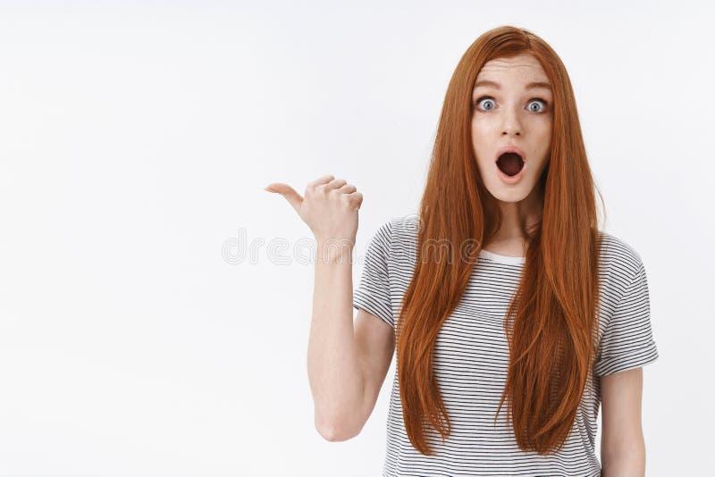 Shocked ha impressionato giovane fissare che domandato degli occhi azzurri della ragazza dello zenzero il pollice indicante sgome fotografia stock