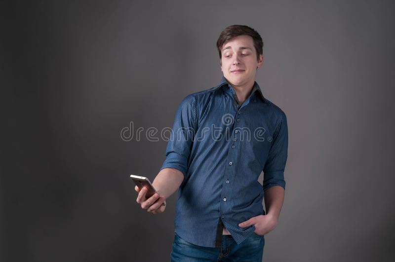 Shocked handsome young man in blue shirt smiling and looking at smartphone. On grey background with copy space royalty free stock photography