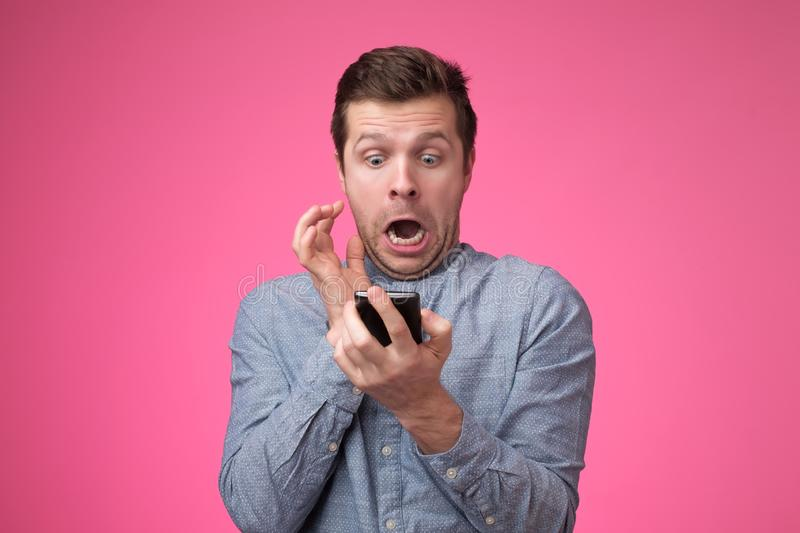 Young man standing, using smartphone and watching video with amazed face. stock photography