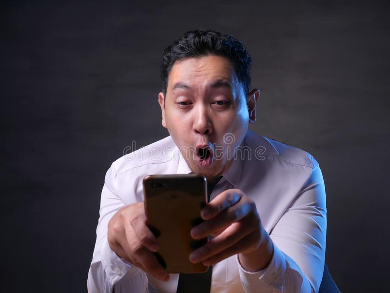 Shocked Happy Man Looking at Smart Phone. Portrait of happy funny Asian man shocked or surprised with mouth open, good news on smart phone concept, amazed royalty free stock photography