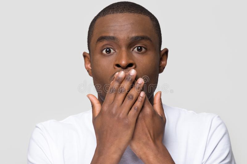 Shocked horrified african man covering mouth with hands feel scared royalty free stock image