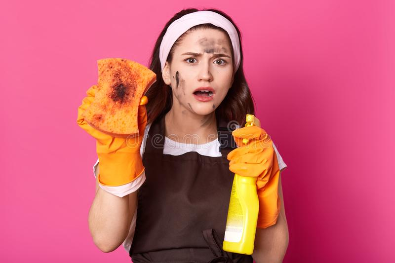 Shocked impressed cute young lady showing dirty washcloth, holding detergent in yellow bottle, opening mouth widely, wearing white royalty free stock images