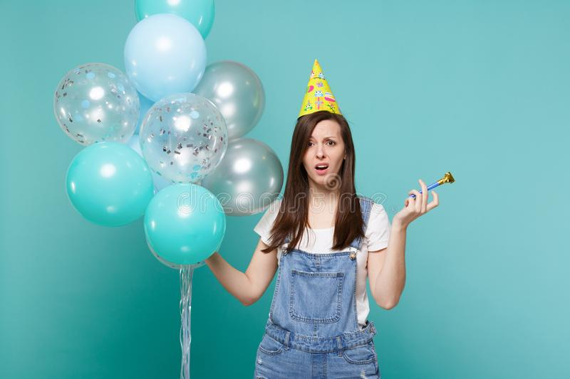 Shocked irritated young woman in denim clothes, birthday hat holding pipe celebrating with colorful air balloons. Isolated on blue turquoise background royalty free stock photos