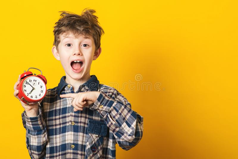 Shocked kid boy holding clock alarm, copy space. Kid isolated over yellow background. Time for school. Little student overslept. T stock photos