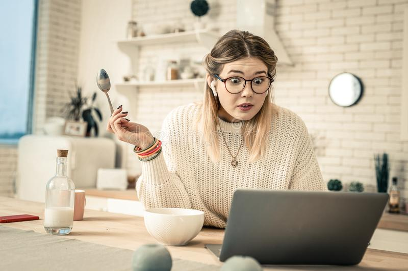 Shocked lady in clear glasses looking on laptop with widely-opened eyes royalty free stock images