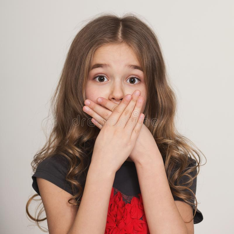 Shocked little girl covering her mouth by hands stock photo