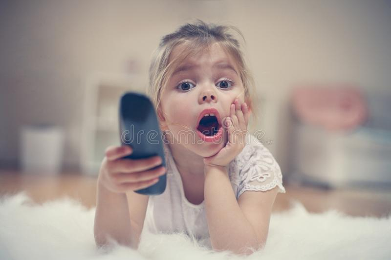 Cute little girl lying on floor. Shocked little girl watching TV lying on floor with remote control in hand royalty free stock photography