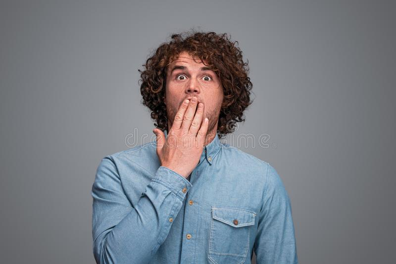 Shocked male covering mouth. Attractive guy with curly hair covering mouth and looking at camera with astonished face expression while standing on gray stock photography