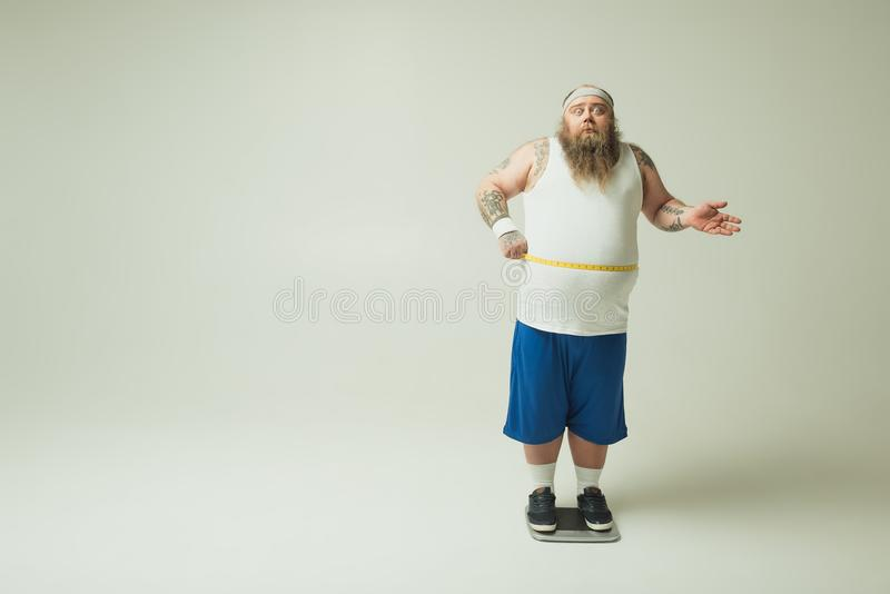 Shocked male fatty taking measurements of his belly stock photography