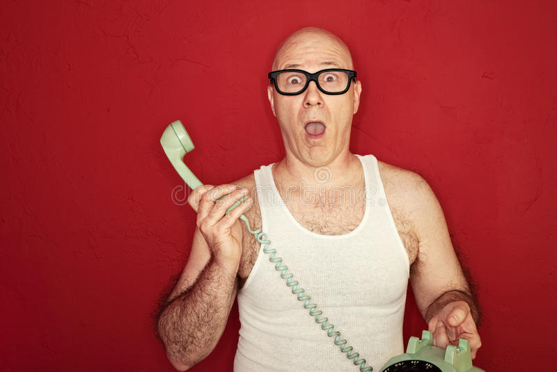 Shocked Man. Shocked bald Caucasian man holds telephone over maroon background stock images