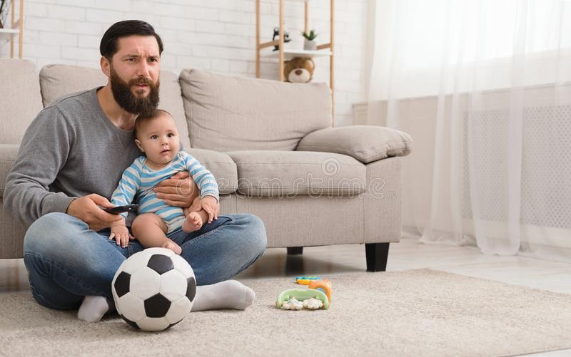 Shocked man and little boy watching soccer game on tv stock photography