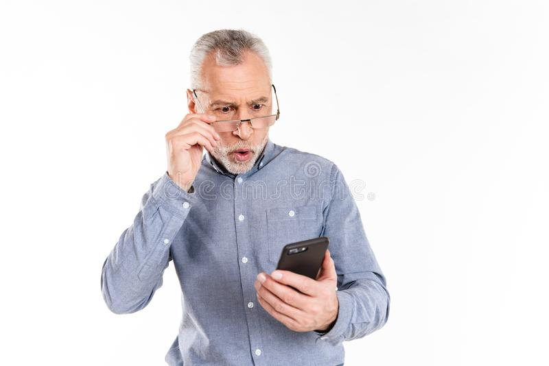 Shocked man looking at smartphone isolated. Shocked mature man in eyeglasses looking at smartphone isolated over white stock photos