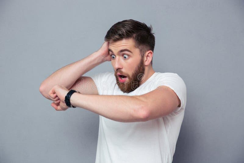 Shocked man looking on wrist watch. Portrait of a shocked man looking on wrist watch over gray background stock image