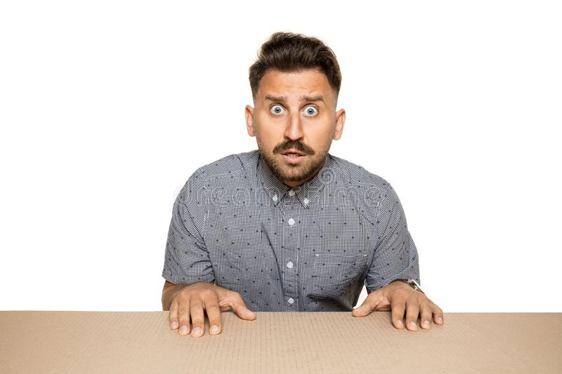 Shocked man opening the biggest postal package. Shocked and astonished man opening the biggest postal package. Excited young male model on top of cardboard box royalty free stock photo