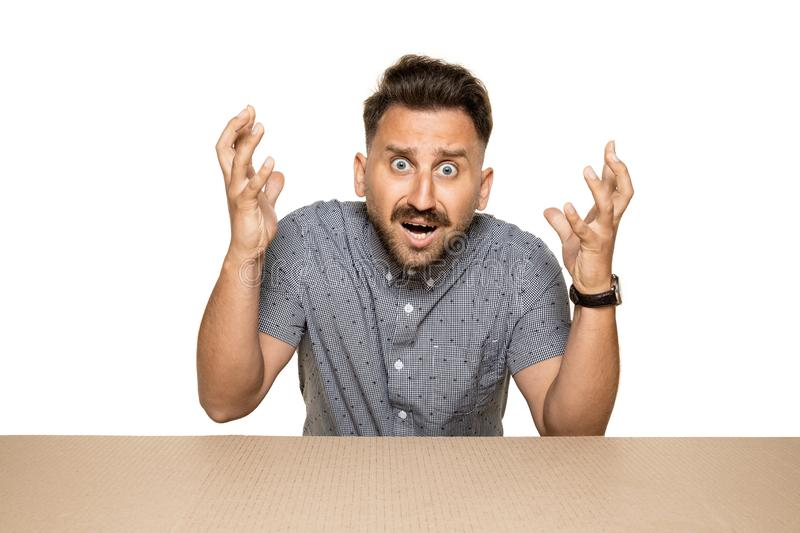 Shocked man opening the biggest postal package. Shocked and astonished man opening the biggest postal package. Excited young male model on top of cardboard box stock photography