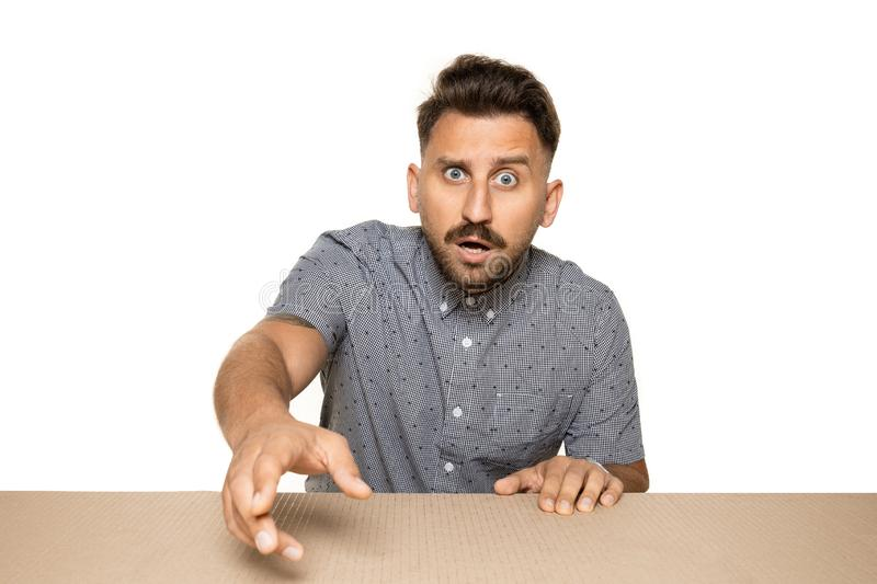 Shocked man opening the biggest postal package. Shocked and astonished man opening the biggest postal package. Excited young male model on top of cardboard box royalty free stock image