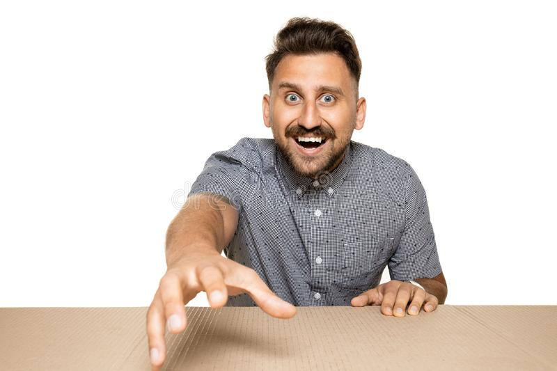 Shocked man opening the biggest postal package. Shocked and astonished man opening the biggest postal package. Excited young male model on top of cardboard box stock photo