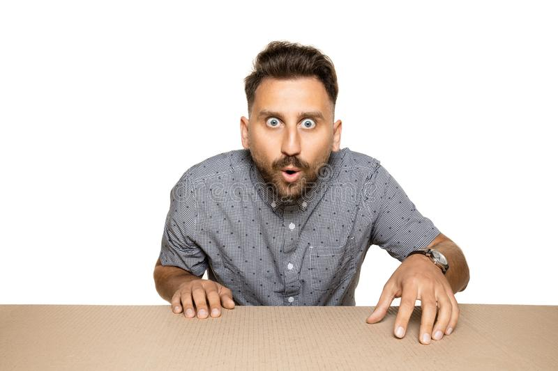Shocked man opening the biggest postal package. Shocked and astonished man opening the biggest postal package. Excited young male model on top of cardboard box royalty free stock photos