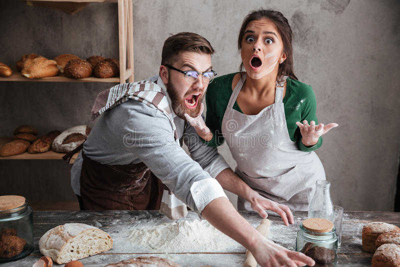 Shocked man and woman standing near table with flour royalty free stock images