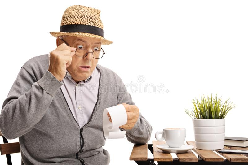 Shocked mature man seated at a coffee table looking at the bill royalty free stock photos