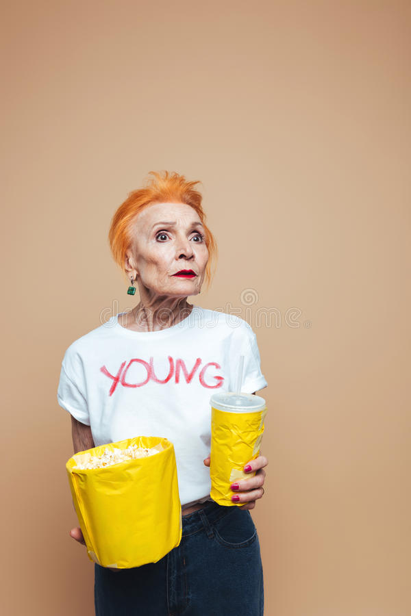 Shocked mature redhead fashion woman. Picture of shocked mature redhead fashion woman standing isolated at studio eating popcorn and drinking aerated water stock photography
