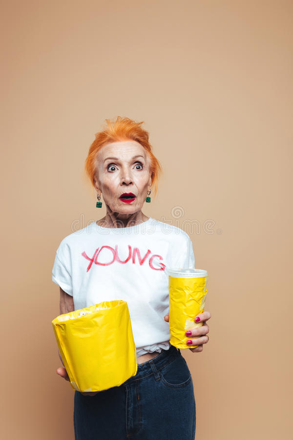 Shocked mature redhead fashion woman. Picture of shocked mature redhead fashion woman standing isolated at studio eating popcorn and drinking aerated water stock photo