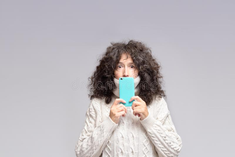 Shocked mature woman with smartphone in front of mouth. A woman in her fifties with a shocked expression, round eyes is holding a smartphone in front of her stock photos